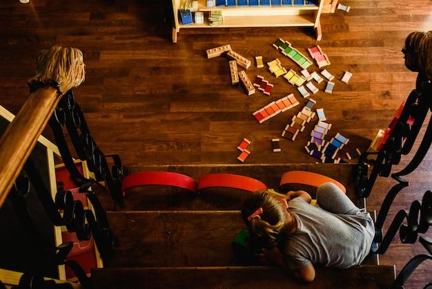 Meisje die met montessorimaterialen thuis gebruiken en spelen