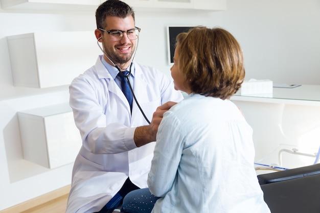 Meisje die met stethoscoop door pediater in het bureau worden onderzocht.