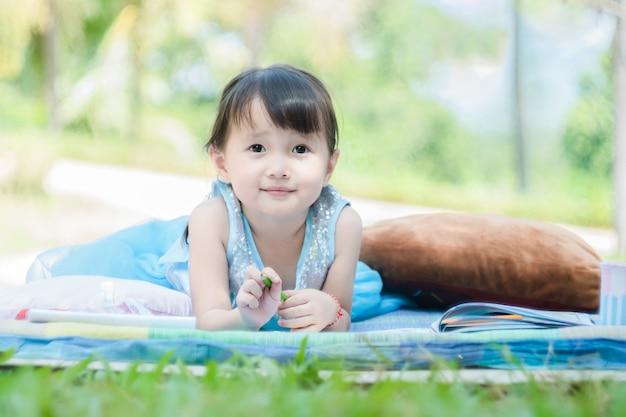 Meisje die met tekeningsboek liggen op mat in park met gelukkig gezicht