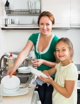 Meisje die moeder afwassen helpen