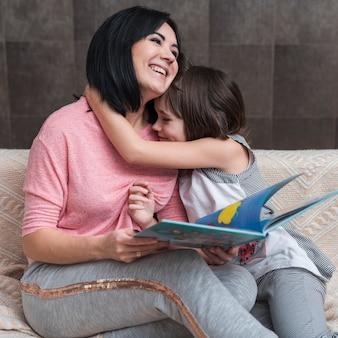 Meisje die moeder met boek op laag koesteren
