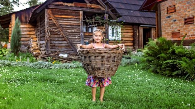 Meisje die oogst in het landbouwbedrijf helpen dragen door een mand te houden