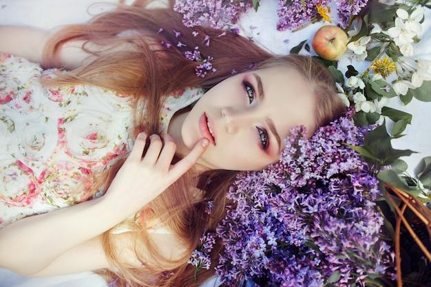 Meisje die op gras in takken van lilac bloemen liggen