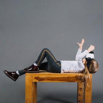 Meisje die op houten lijst liggen die virtuele werkelijkheidsglazen dragen die handgebaar maken tegen grijze achtergrond