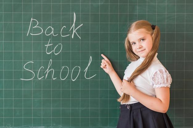 Meisje die op terug naar school het van letters voorzien op rugplank richten