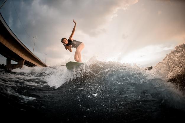 Meisje die op wakeboard op de rivier op de achtergrond van de brug berijden die één hand toenemen
