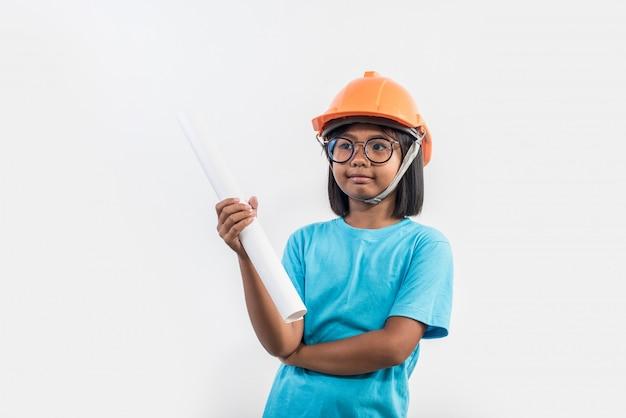 Meisje die oranje helm in studioschot dragen