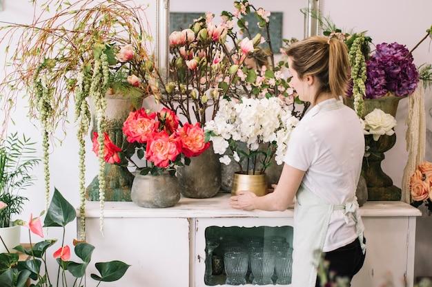 Meisje die prachtige bloemensamenstelling in winkel maken