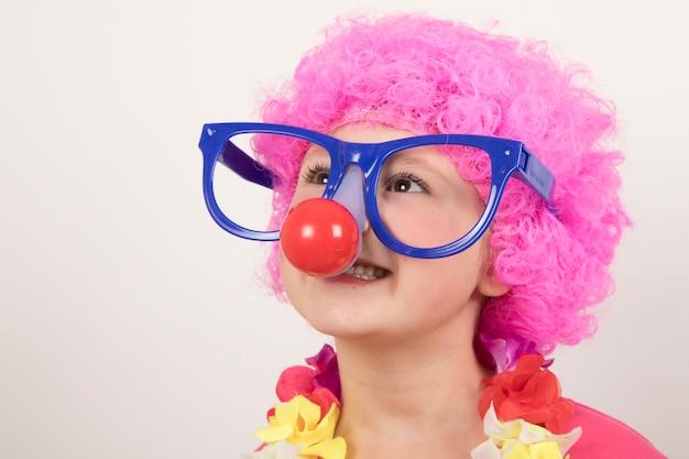 Meisje die pruik en clownglazen dragen en voor carnaval glimlachen