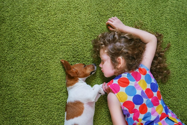 Meisje die puppyhefboom russell omhelzen en op groen tapijt liggen. hoge bovenaanzicht.