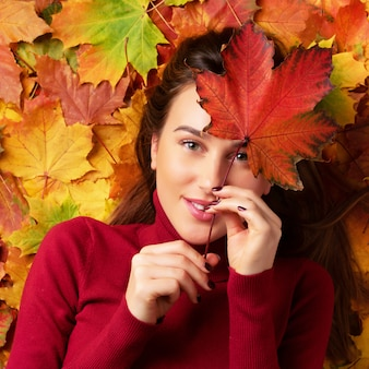 Meisje die rood esdoornblad houden over kleurrijke gevallen bladerenachtergrond in hand.