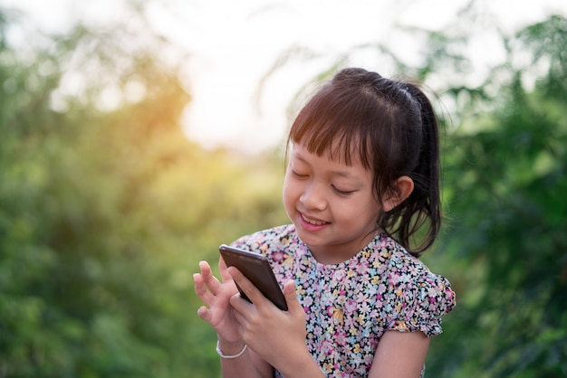 Meisje die smartphone met glimlach gebruiken
