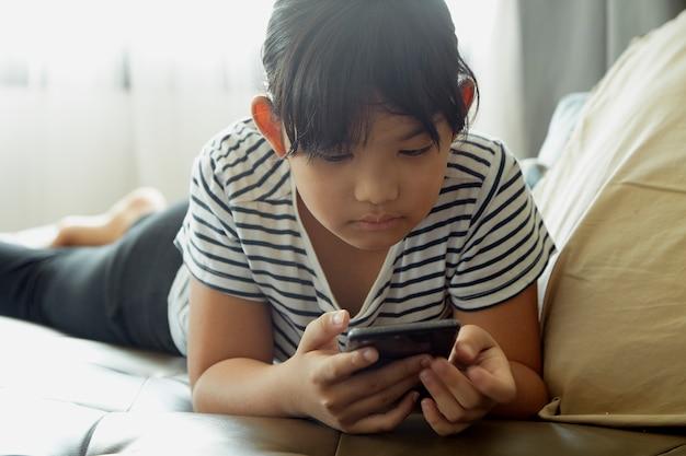 Meisje die smartphone thuis gebruiken