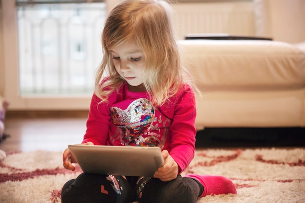 Meisje die tablet op woonkamervloer gebruiken