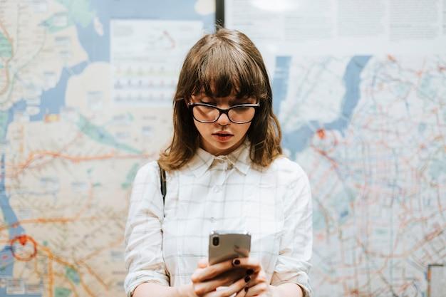 Meisje die terwijl het wachten op een trein bij een metroplatform texting