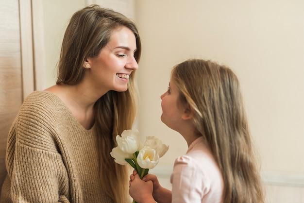 Meisje die tulpenbloemen geven aan moeder
