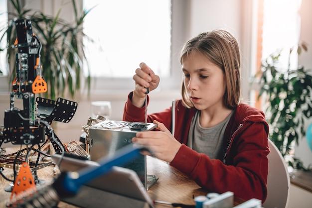 Meisje die voeding aanpassen en robotica leren