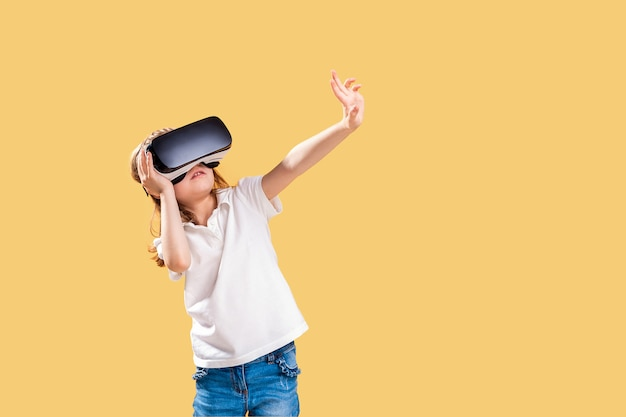 Meisje die vr-hoofdtelefoonspel op geel ervaren. verraste emoties op haar gezicht. kind met een gaminggadget voor virtual reality.