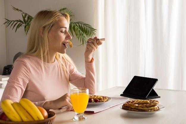Meisje die wafels eten die op tablet letten