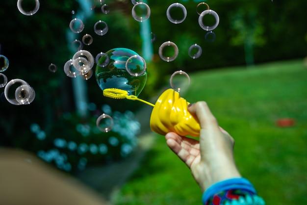 Meisje die zeepbels in de binnenplaats in de zon spelen
