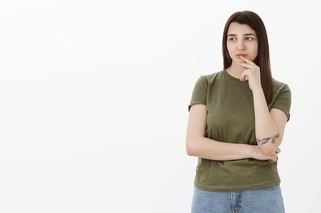 Meisje diep nadenkend uit elkaar als kijkend met interesse, bedachtzaam aan de linkerkant van de kopie ruimte, lip aanraken met vinger kruisarm over lichaam kijkt vastberaden en veroordelend over grijze muur
