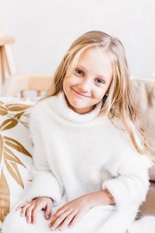 Meisje, dochter, baby zittend op de bank in een lichte warme trui, lang blond haar, europese uitstraling en licht interieur