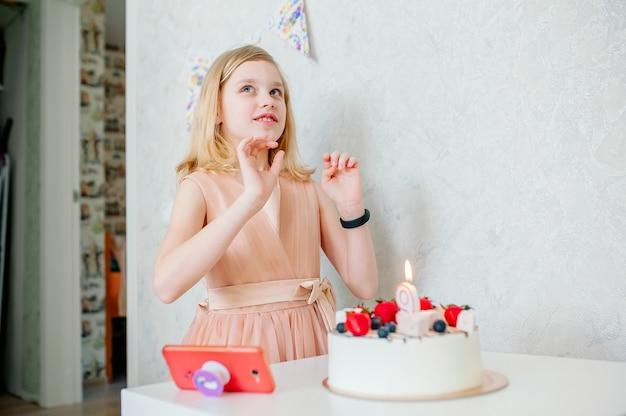 Meisje doet een wens, er staat een taart op tafel