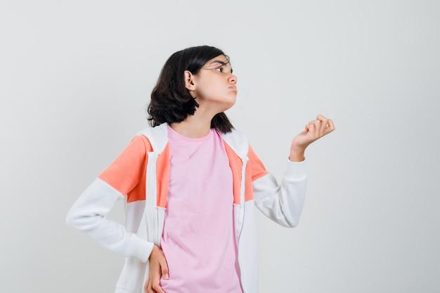 Meisje doet geldgebaar in t-shirt, jasje en zoekt armoedig. vooraanzicht.