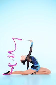 Meisje doet gymnastiek dans met gekleurd lint op blauw