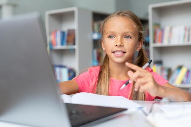 Meisje doet haar huiswerk terwijl ze op de laptop kijkt
