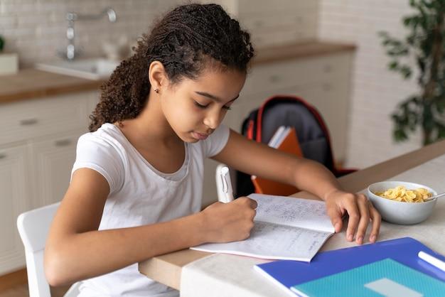 Meisje doet haar huiswerk tijdens het ontbijt