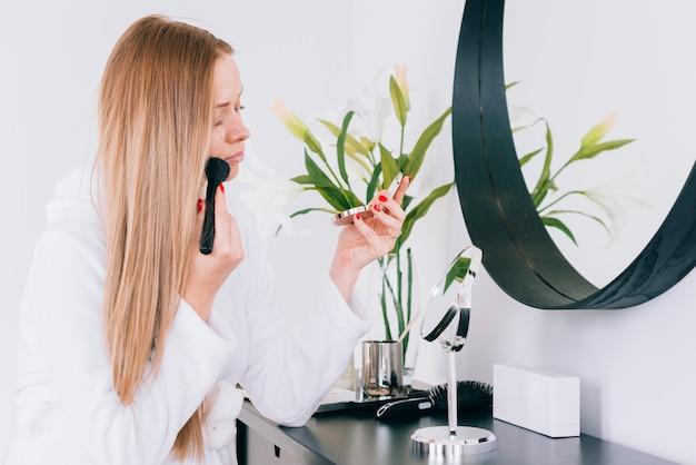 Meisje doet haar make-up in de badkamer