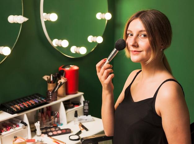 Meisje doet haar make-up in een groene kamer