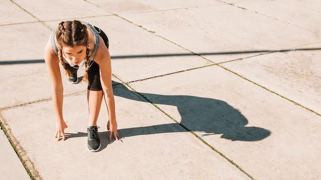 Meisje doet hurken begin in zonlicht