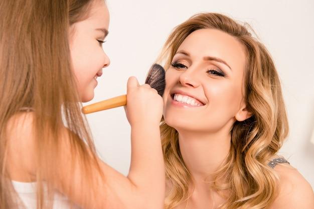 Meisje doet make-up aan haar vrolijke moeder