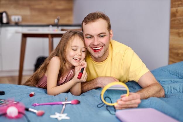 Meisje doet make-up voor haar jonge vader. papa brengt thuis vrije tijd door met haar dochter.