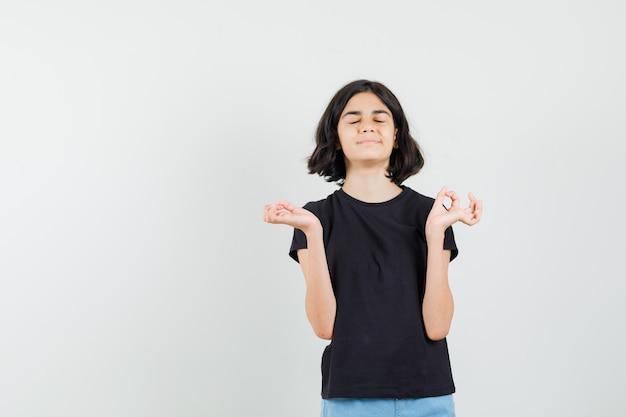 Meisje doet meditatie met gesloten ogen in zwart t-shirt, korte broek en op zoek naar rustige, vooraanzicht.