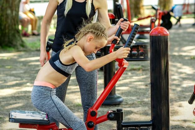 Meisje doet oefeningen op simulator onder toezicht van jonge vrouw coach in het park