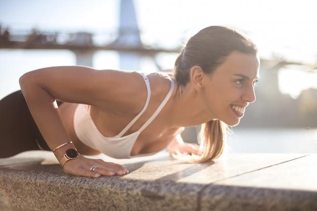 Meisje doet push ups op straat, langs de rivier,