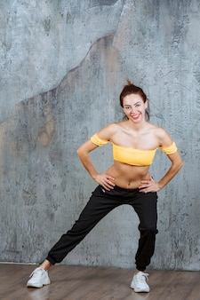Meisje doet rug- en beenrekoefeningen op een yogamat.