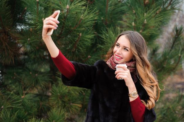 Meisje doet selfie in herfst park, aantrekkelijke vrouw wandelen in het park in herfstdag