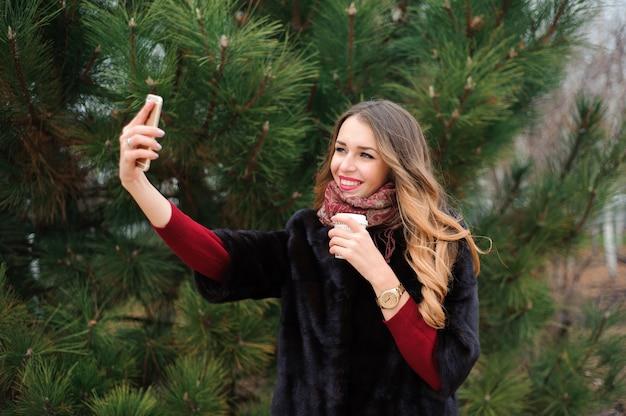 Meisje doet selfie in herfst park, aantrekkelijke vrouw wandelen in het park