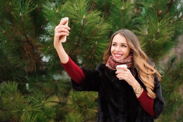Meisje doet selfie in herfst park buiten