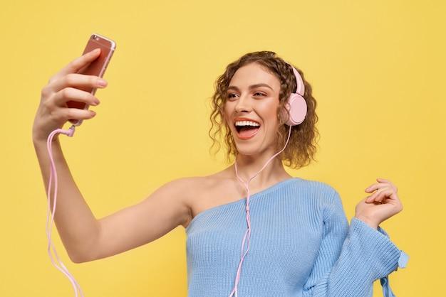 Meisje doet selfie, luisteren naar muziek, poseren.