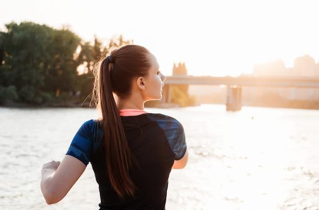 Meisje doet warming-up in de buurt van rivieroever bij zonsondergang