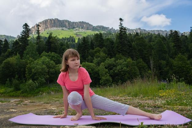 Meisje doet yoga in de natuur op een achtergrond van bergen