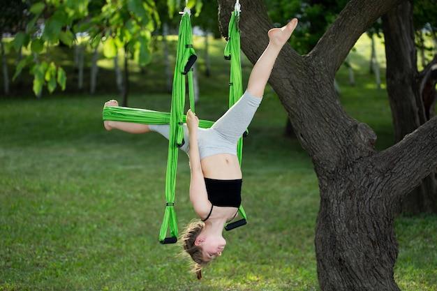 Meisje doet yoga-oefeningen met een hangmat in het park