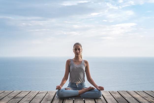 Meisje doet yoga op de achtergrond van de zee