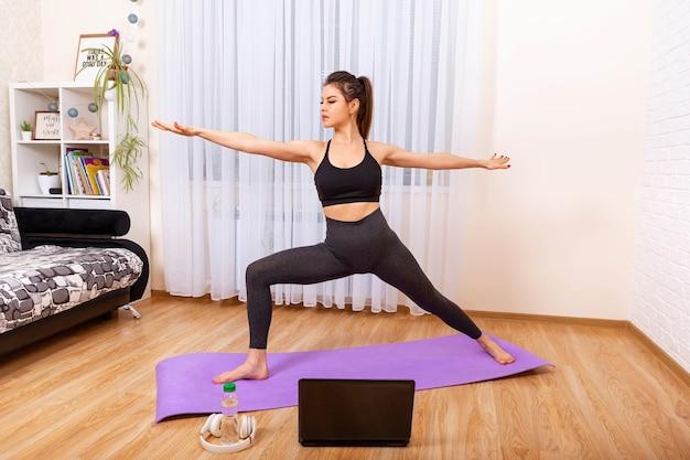Meisje doet yoga thuis yoga online op de laptop gezonde levensstijl