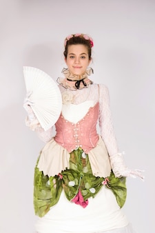 Meisje draagt een 19e-eeuwse mode-stijl, dame high society renaissance korset en lange rok die zonventilator blij en glimlachend vasthoudt